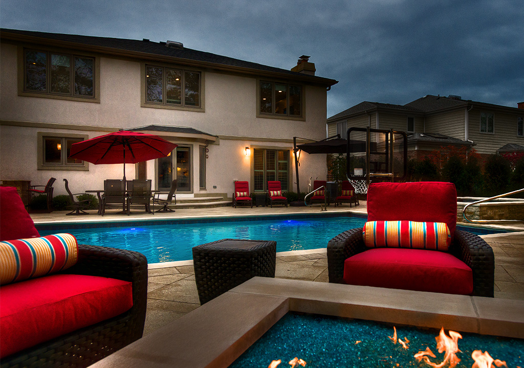 Backyard pool and fire pit at dusk
